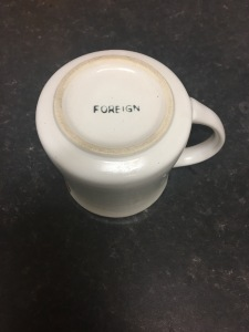 """The base of an old mug with the word """"Foreign"""" on it, meaning foreign made."""