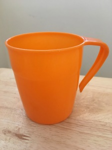 "An orange Twinco Plastic Mug. Circa 1970s. Photograph by author 17 Feb 2017. On bottom it reads ""Twinco No. 2138 REG'D DESIGN No 938656 MADE IN ENGLAND"". Front view."