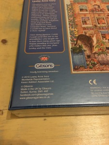 Gibsons Peeping Tom cat themed jigsaw puzzles, 500 pieces. Made in the UK and are labelled as such. Photograph by author. Rear of box view, close up of country of origin label.