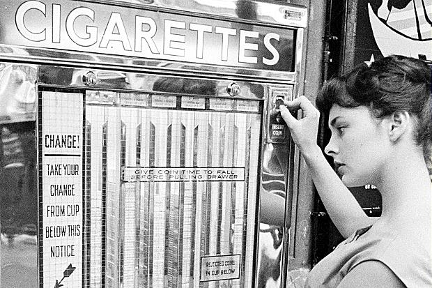 A young woman buys a packet of cigarettes from a vending machine. c.1950s