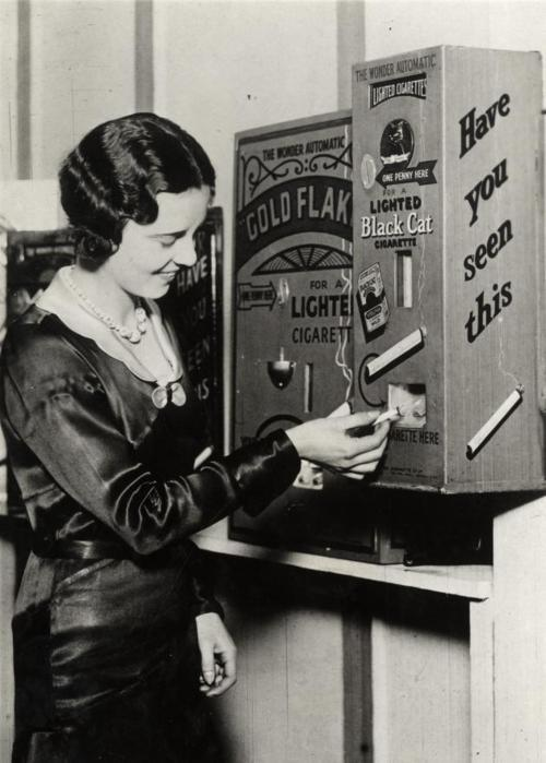 A cigarette vending machine in England that delivered a lit cigarette for a penny, 1931.