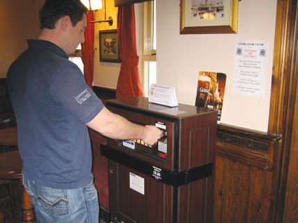 A man buys a packet of cigarettes from a vending machine in an unknown pub in the UK. Undated but c.2011.