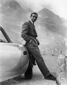 Connery wears Anthony Sinclair barleycorn tweed hacking jacket and plain front, cavalry twill trousers with frogmouth pockets, in Goldfinger, 1964