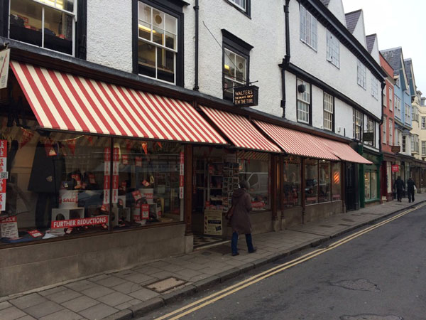Walters in the Turl, February 2015 - Walters, the famous exclusive University outfitters in Oxford, have given their frontage a fresh look, whilst retaining the traditional patina of the building, by refurbishing their existing Victorian commercial awnings with new, bold red and white block stripe canvas type covers. The traditional Victorian awning has been manufactured in the London factory of Deans Blinds & Awnings UK Ltd and fitted by them.