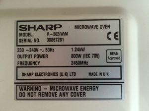 A vintage Sharp microwave oven model R-202(W)M. Made in U.K. View of label on rear.