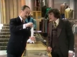 "Screenshot from the Are You Being Served Pilot (1972; restored into colour 2009) - Captain Peacock (played by Frank Thornton) shows Mr Lucas (played by Trevor Bannister) how to flute a handkerchief for display in a top pocket. ""The effect is casual but smart"" Captain Peacock tells us"