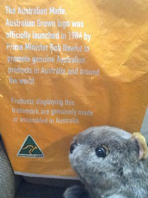A carrier bag advertisiing the Australian Made, Austrain Grown logo, togther with Bruce, an Australian made toy wombat. Photograph by author.